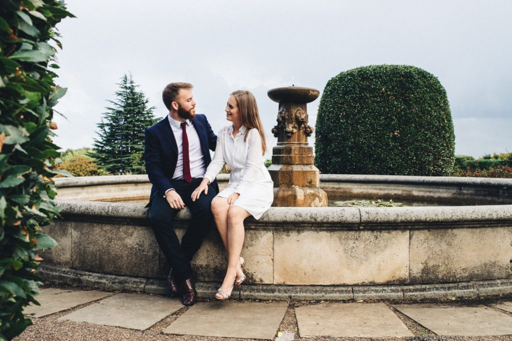 Elegant couple sitting on fountain in Alexandra Palace Gardens
