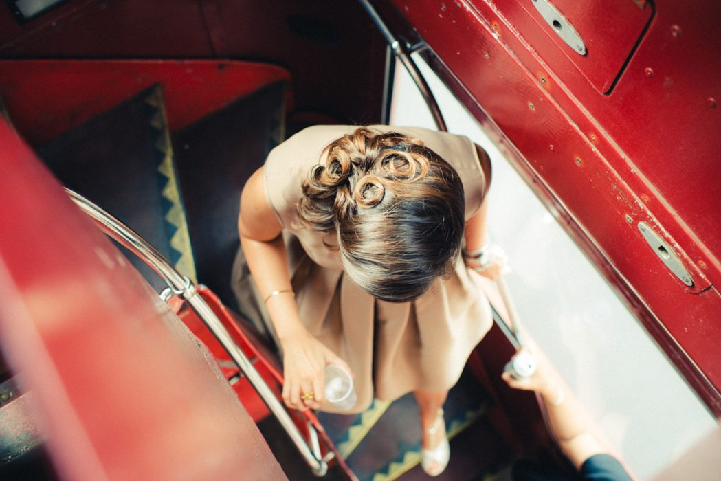 Elegant lady going down stairs of a double deck bus in a london wedding