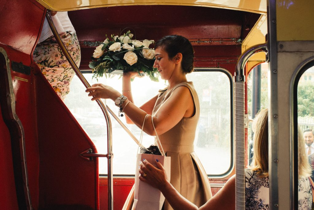 Lady climbing london deck bus with flowers London Wedding