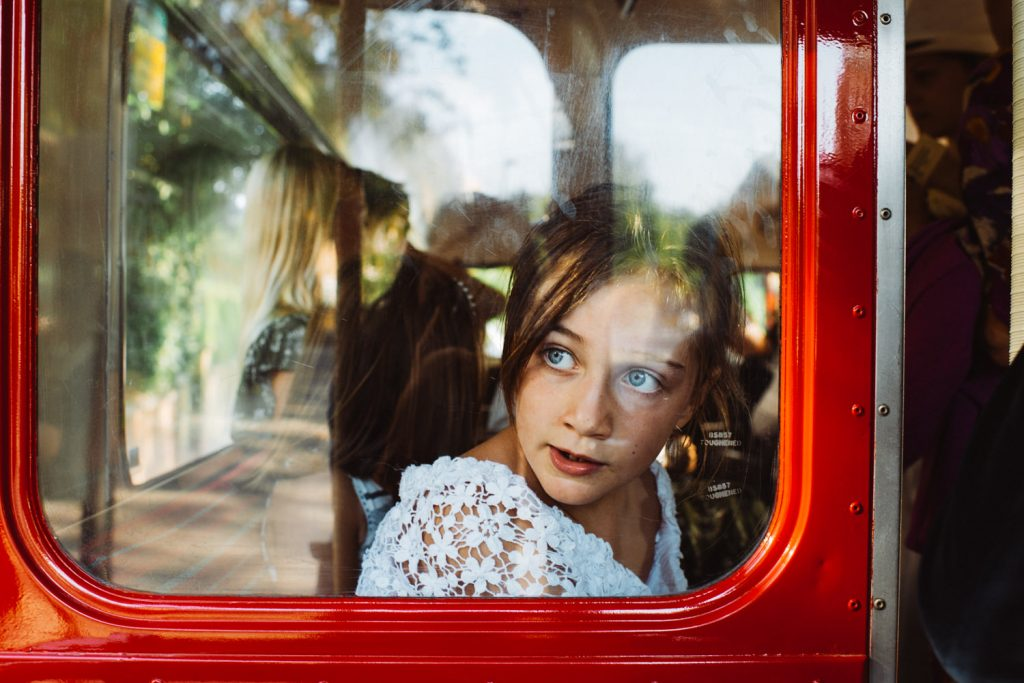 Misty, young girl in vintage red bus at wedding
