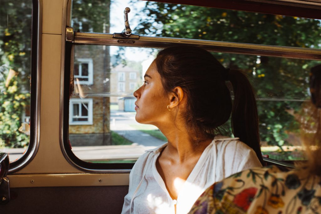 Young woman in London red bus during wedding